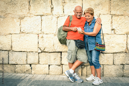 Leinwanddruck Bild Happy senior couple having fun with a modern smartphone
