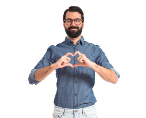 Young hipster man making heart sign
