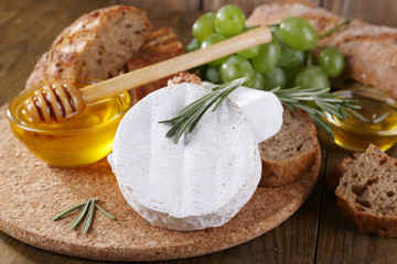 Camembert cheese, bread, honey and grapes