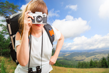 young beautiful woman hiker looking through camera on mountain i