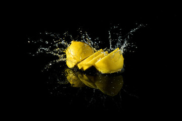 Sliced lemon splash on black background © cherryandbees