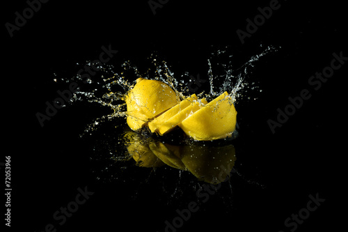 Sliced lemon splash on black background - 72053966