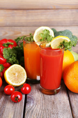 Carrot and tomato juice in glasses and fresh vegetables