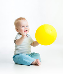 Smiling baby boy with yellow ballon in his hand