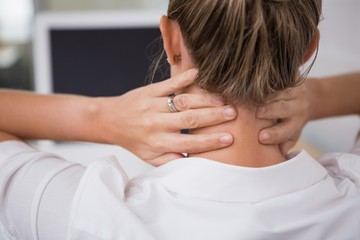 Mid section of businesswoman suffering from neck ache