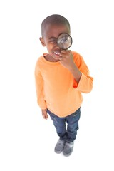 Cute boy looking through a magnifying glass