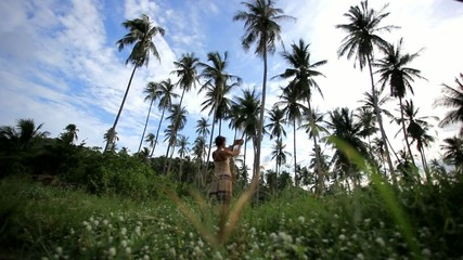 Woman takes pictures of palm trees in the jungle on Koh Samui.