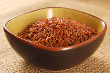 red rice in bowl on hessian fabric