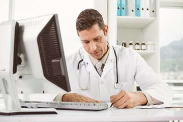 Doctor working at desk in medical office