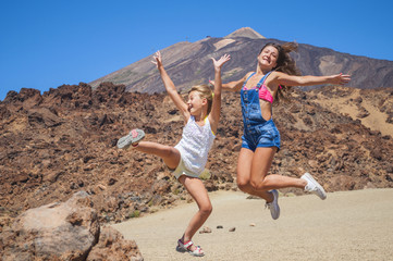 girl and woman jumping over the valley among mountains Teide