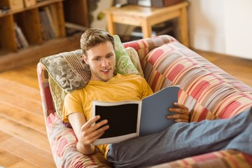 Young man reading magazine on his couch