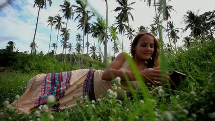 Young beautiful smiling woman lies on lawn and talks by mobile