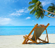 Tropical beach and woman relaxing sitting on the bamboo chair