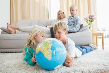 Siblings looking at globe on the floor
