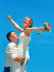 Groom holding bride in his arms on background the sky