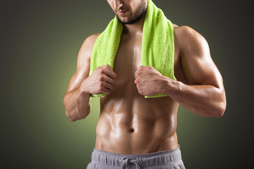 Fitness man holding a green towel against dark background