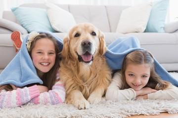 Sisters lying on rug with golden retriever under a blanket
