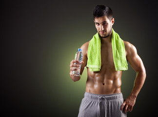 Fitness man holding a bottle of fresh water on dark background