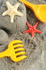 Sandcastle with starfish on sandy beach background