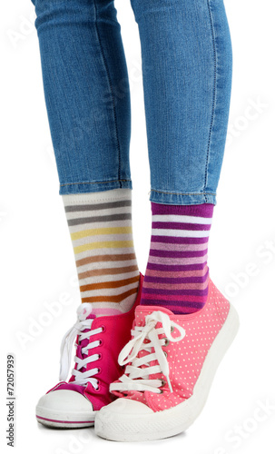 canvas print picture Female legs in colorful socks and sneakers isolated on white