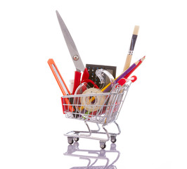 Shopping cart full of school material, isolated on white backgro