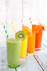 Fruit and vegetable juice in glasses and pieces of fresh fruits