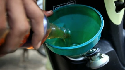 Pouring gasoline in the motorbike from bottle through a funnel