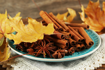 Cinnamon sticks and stars anise with yellow leaves
