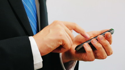 Man wearing a suit using a cellphone