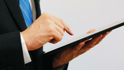 Man wearing a suit using a tablet