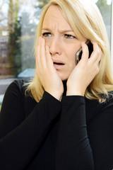 Frau entsetzt am Telefon