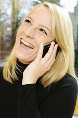 Blonde Frau lacht am Telefon