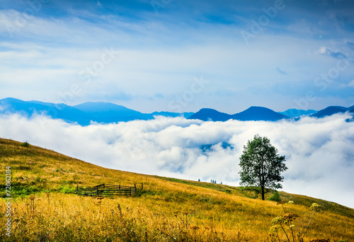 Fotobehang Heuvel Amazing mountain landscape with fog and a haystack