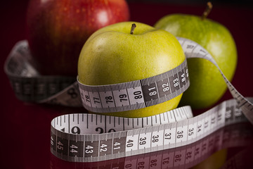 Apples with measuring tape over red background