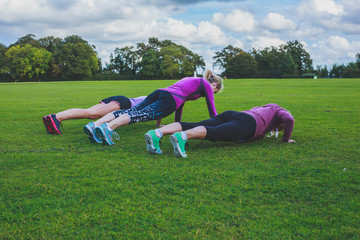 Three women doing push ups in park