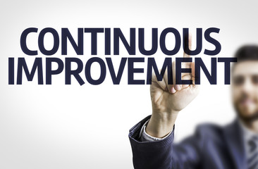 Business man pointing the text: Continuos Improvement