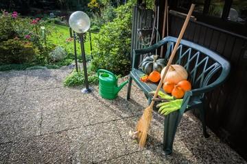 Terrasse im Oktober mit Gartenbank und Kürbissen