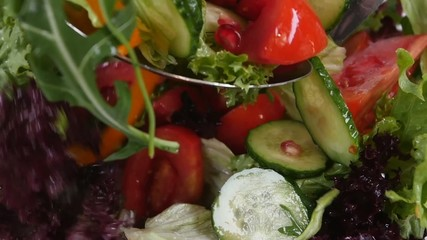 Fresh mixed vegetables falling into bowl of salad isolated on