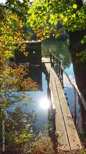 canvas print picture Hütte am See, die Sonne spiegelt sich im Wasser