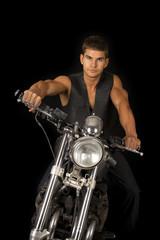man in vest motorcycle on black serious look