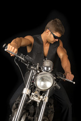 man on motorcycle black vest dark glasses look down