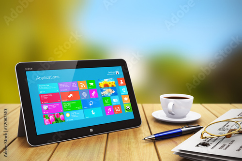 Tablet computer with business objects on wooden table outdoors - 72067510