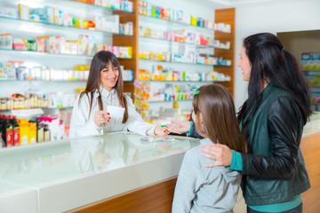Pharmacist giving vitamins to child girl in pharmacy