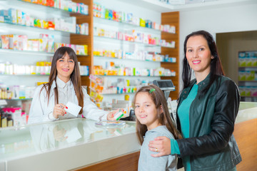 Pharmacist giving vitamins to child girl in pharmacy