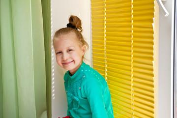 Девочка сидит у окна с жалюзями
