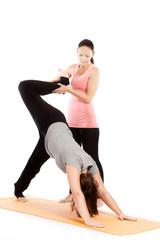 Yogalehrerin gibt Hilfestellung beim Training