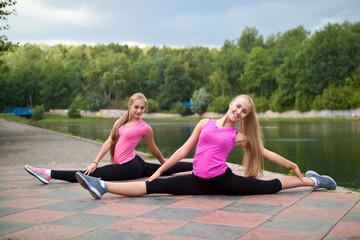 Две девушки сидят на шпагате