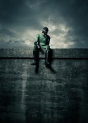 Pensive superhero on concrete wall