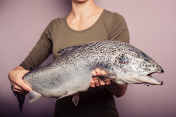 Young woman holding a big salmon