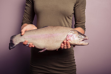 Young woman holding a rainbow trout